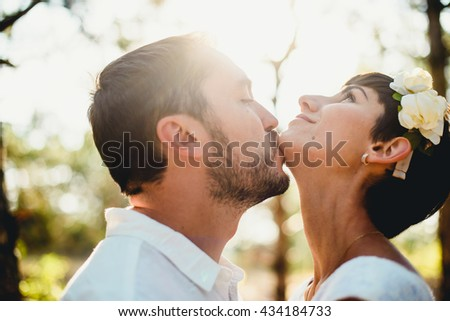 The tenderness couple in love kissing in the forest - stock photo