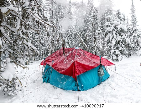 the tent is heated with a pipe in the winter forest - stock photo