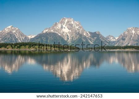 The Teton Range reflected in the Jackson Lake, Grand Teton National Park - stock photo