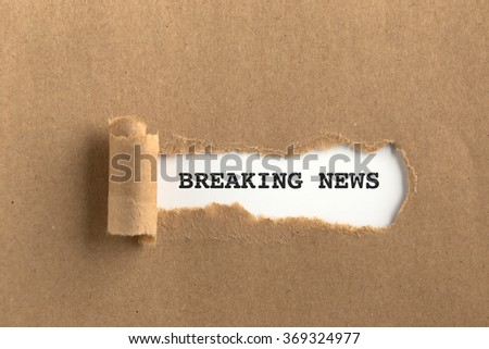 The text BREAKING NEWS behind torn brown paper - stock photo