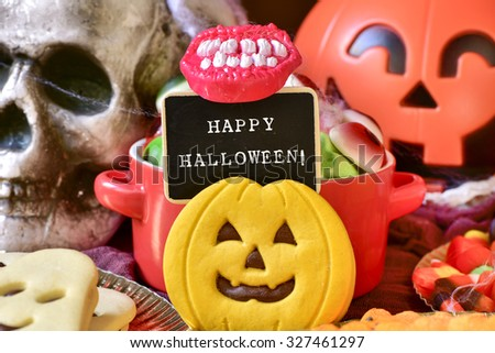 the text happy halloween written in a chalkboard, different Halloween candies and cookies, and some scary ornaments, such as a skull or a carved pumpkin - stock photo