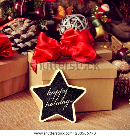 the text happy holidays written in a star-shaped chalkboard with some gifts and a pile of different christmas ornaments, such as baubles, stars and pine cones in the background - stock photo