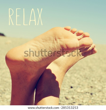 the text relax and the bare feet of a young caucasian man relaxing in a shingle beach, with a retro look - stock photo