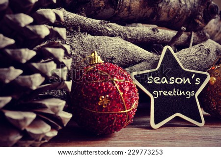 the text seasons greetings written in a star-shaped blackboard and some christmas balls, pinecones and a pile of logs in the background - stock photo
