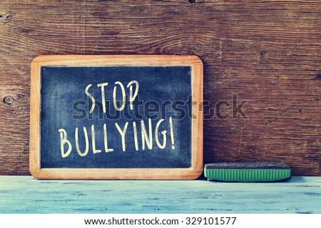 the text stop bullying written with chalk in a chalkboard and an eraser on a blue rustic wooden desk in a classroom - stock photo