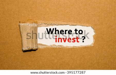 The text Where to invest appearing behind torn brown paper - stock photo