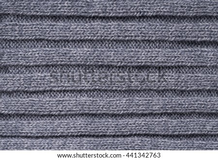 The texture of a knitted woolen cloth is gray, with a ribbed pattern stripes. background - stock photo