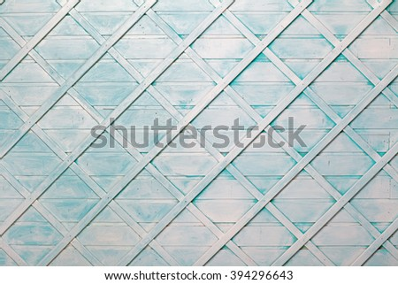 The texture of the painted blue wooden surface with a grid of thin strips - stock photo