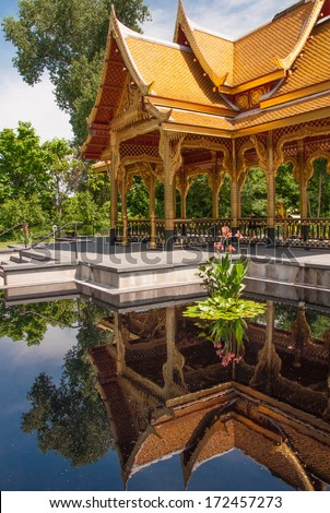 The Thai Pavilion in a Madison, Wisconsin public gardens is beautifully reflected in a surrounding pool of water. - stock photo