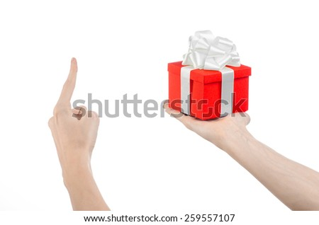 The theme of celebrations and gifts: hand holding a gift wrapped in red box with white ribbon and bow, the most beautiful gift isolated on white background in studio - stock photo
