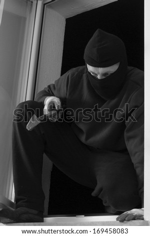 The thief in the balaclava is coming in through the window home - stock photo