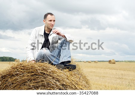 The thoughtful man on a stack of straw against a field and the sky - stock photo