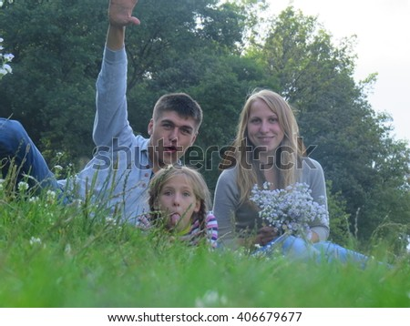 The three - a young family in the grass. - stock photo