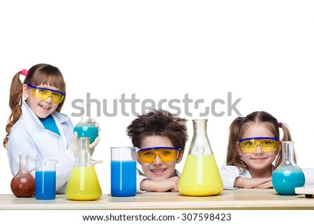 The three cute children at chemistry lesson making experiments on white background - stock photo