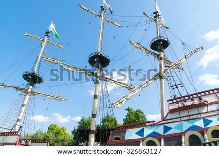 The three masts of a sailboat with furled sails. - stock photo