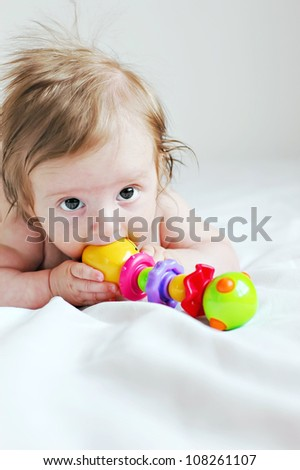 The three-month baby playing with a toy - stock photo