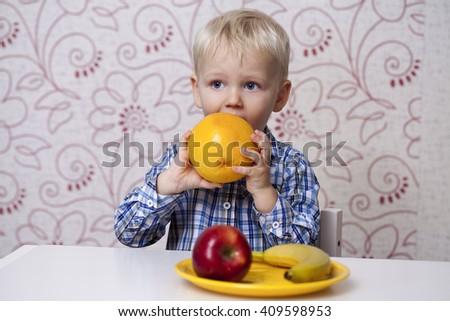 The three-year boy eats a yellow grapefruit at home - stock photo