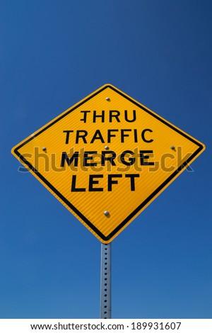 "The ""Thru Traffic Merge Left"" street sign in the Californian sun. - stock photo"