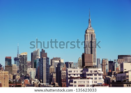 The tight cluster of skyscrapers habituating midtown Manhattan with the famous Empire State Building most prominent, as seen viewing north from the West Village. - stock photo