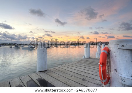 The timber pier at Leichhardt Park views over Iron Cove and moored boats at sunset - stock photo