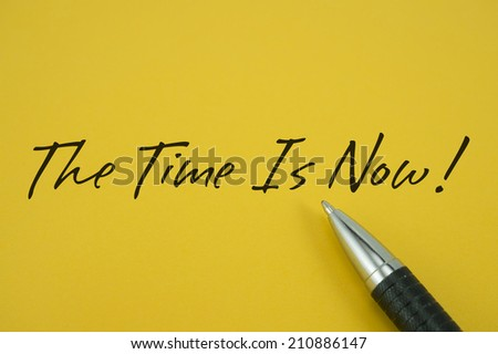 The Time Is Now! note with pen on yellow background - stock photo