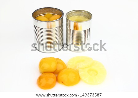 The tins with peaches and pineapples on the white background - stock photo