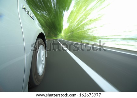 The tire of the hybrid car which runs in fresh green - stock photo