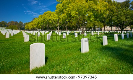 The tombstones of Las Angeles National Cemetery lay under a sun-filled summer sky. - stock photo
