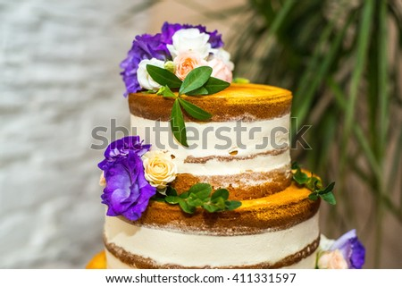The top of a wedding cake, decorated with flowers. Naked cake, decorated with flowers. Rustic wedding. - stock photo