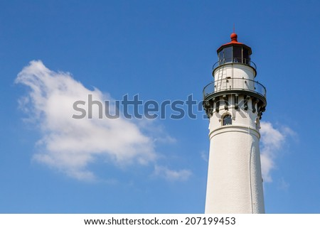 The top of the beautiful Wind Point Lighthouse, near Racine, Wisconsin, is backed by a blue, cloud-draped sky. - stock photo
