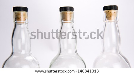 The tops of three whiskey bottles with corks against grey white background - stock photo