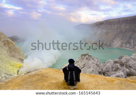 The Tourist relaxing on a rock at Kawah Ijen Volcano,Java island - stock photo