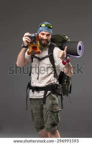 The tourist with camera. Portrait of a male fully equipped tourist with backpack. He photographing something on gray background,  - stock photo