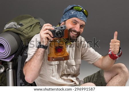 The tourist with camera. Portrait of a male fully equipped tourist with backpack. He sitting and photographing something on gray background,  - stock photo