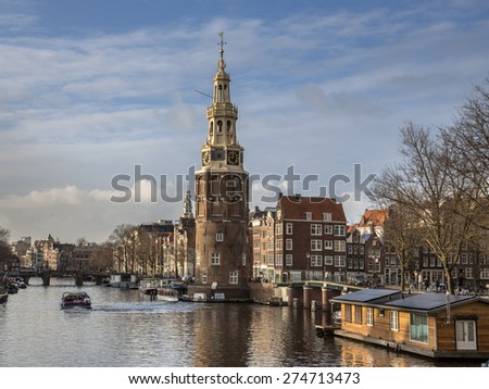 The tower Montelbaanstoren with houseboats and historic canal houses in Amsterdam - stock photo