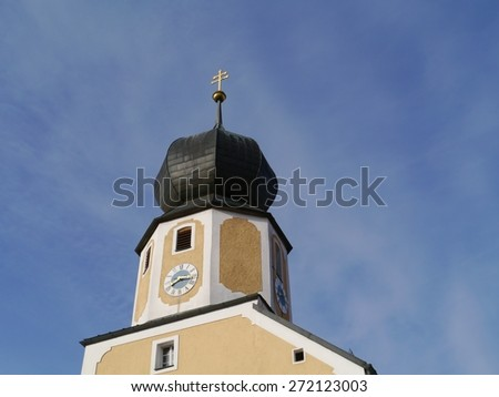 The tower of the medieval church of Parsberg in the county of Neumarkt in Bavaria in Germany opposite a blue sky - stock photo