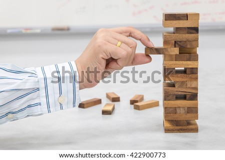 The tower stack from wooden blocks toy and man's hand take one block - stock photo