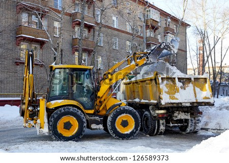 the tractor loads the cleaned snow on the dump truck - stock photo