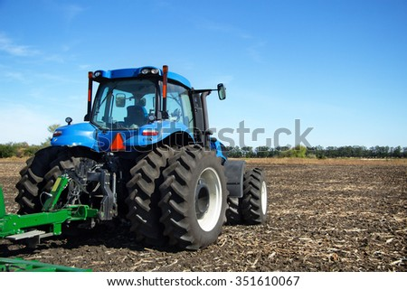 The tractor wheels on the huge field, a farmer riding a tractor, a tractor working in a field, agricultural machinery in the work, tractor against the blue sky - stock photo