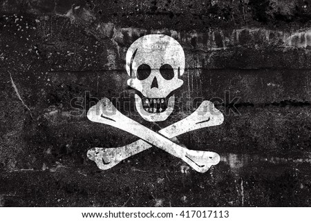 The traditional Jolly Roger of piracy Flag, painted on dirty wall. Vintage and old look. - stock photo