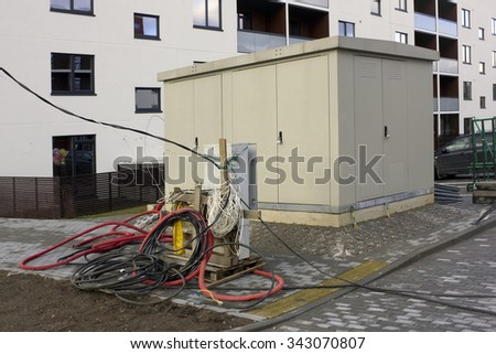 The transformer box and ball of electric cables on street near a new building - stock photo