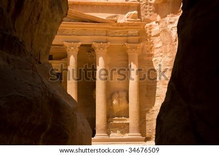 The Treasury seen through the Siq, a narrow canyon path through high rock cliffs, at Petra. - stock photo