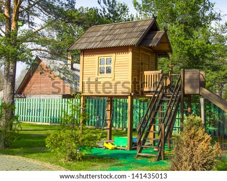The tree house with a staircase and a slide for the children's games - stock photo