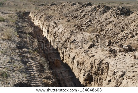 the trench dug in the earth in the desert - stock photo