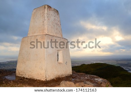 The trig point at top of Arthur's Seat in the morning light overlooking Edinburgh, Scotland. - stock photo