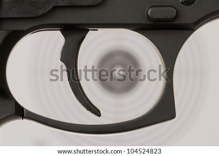 The trigger of a handgun with a shooting target on the background - stock photo