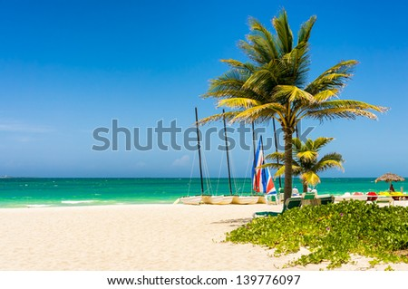 The tropical beach of Varadero in Cuba with coconut palms and colorful sailing boats - stock photo