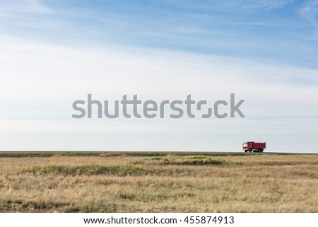 the truck rides on the highway in the desert - stock photo