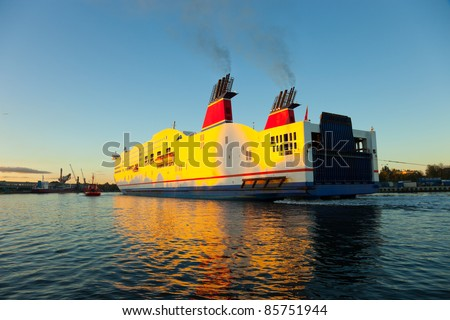 The tugboat helps to a vessel in the port. - stock photo