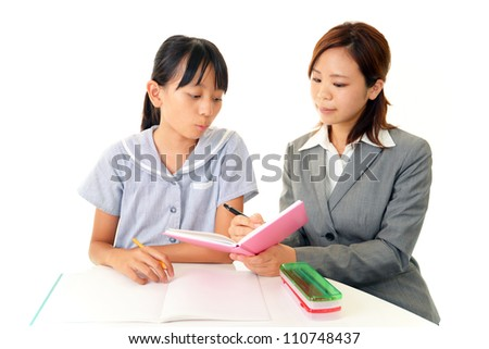 The tutor and the girl are studying hard - stock photo